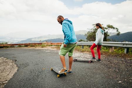tropics: long boarding couple in tropics with mountain view Stock Photo