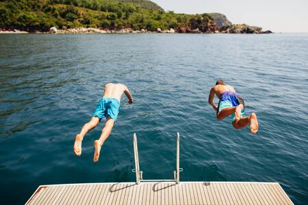 men jumping into sea water from yacht party vacation Stock Photo