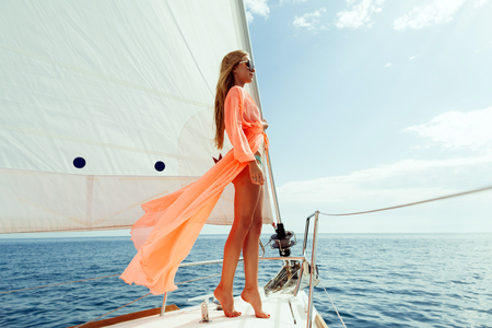 fashion girl yachting in sea with sarong and blue sky sunlight Stock Photo