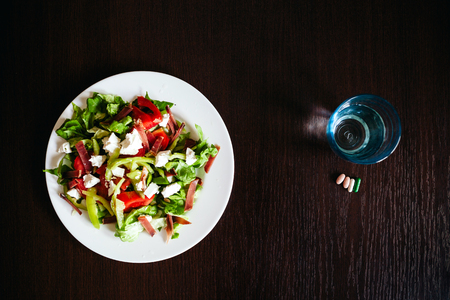 holistic view: green salad with pills and glass of water top view.