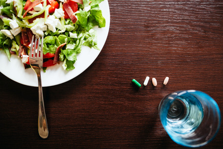holistic view: green salad with pills top view