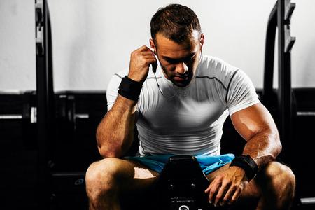 Bodybuilder forte écoute de la musique dans la salle de gym