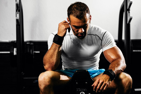 strong bodybuilder listen to music in gym