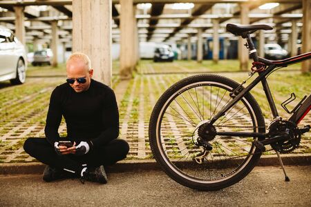 man searching: bicycle man searching in smartphone at parking