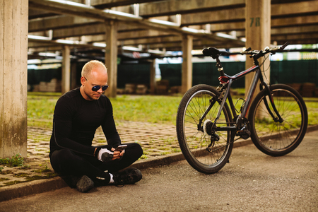 bicycle man searching in smartphone at parking