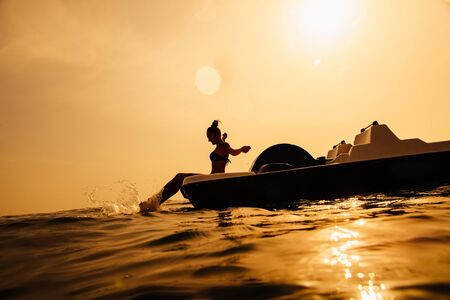 peddle: girl on paddle boat catamaran with sunlight in sea