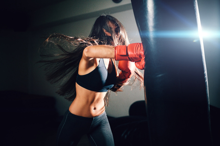 sexy fighter girl punching actively. motion long hair Stock Photo