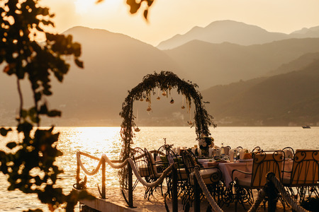 pierce: destination wedding arch and banqouet covered table at sunset pierce with sea and mountain view.  Banqu