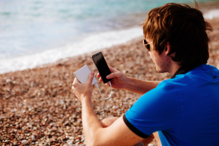 man charging smartphone with powerbank on vacations at sea side