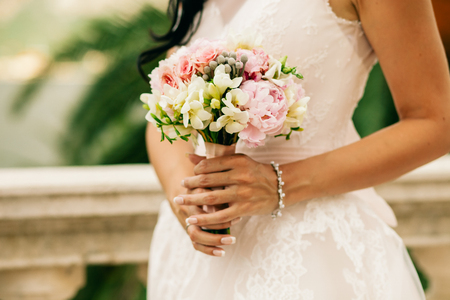 bride hold wedding bouquet of rose peonies and roses. Hands close up