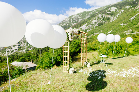 fine art: wedding arch with wedding decoration and sea view. Picturesque wedding location with balloons in fine art style