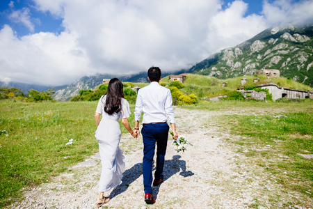 honeymoon wedding couple travel back view. Mountains and sky background in Montenegro
