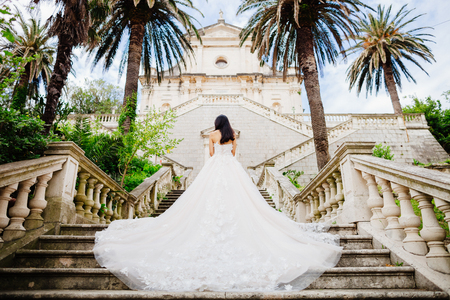 elegant staircase: bride in wedding dress with church background. Back view. Destination wedding