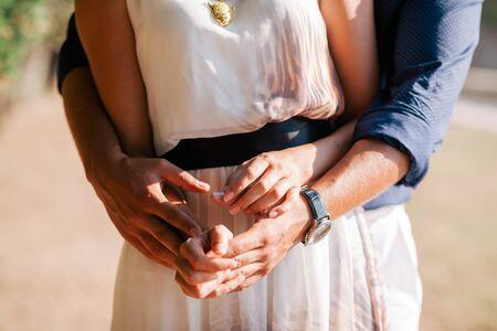 engaged: engaged couple hug together. Close up shot of hands