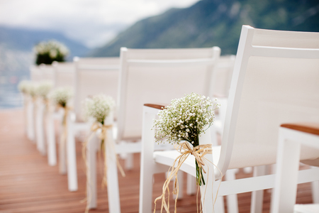 venue: wedding chairs with flowers decoration. Wedding venue ceremony. Stock Photo
