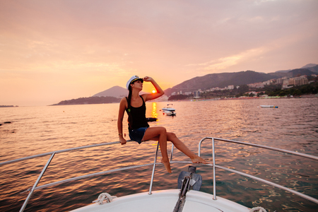 woman travel on yacht at beautiful sunset. Picturesque sunset seascape Stock Photo