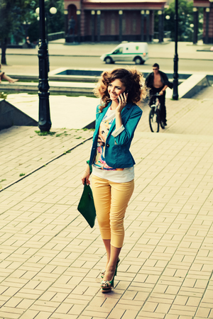 sexy fashion woman talk over smartphone. Woman walk down the street with phone.