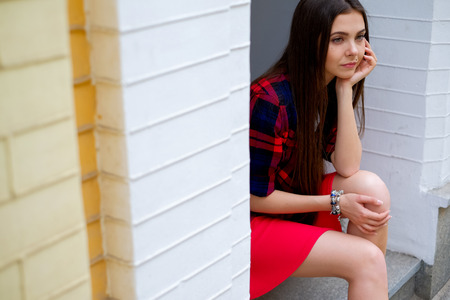 erotical: thoughtful woman in skirt sitting on street. Beautiful long hair woman relax on street Stock Photo