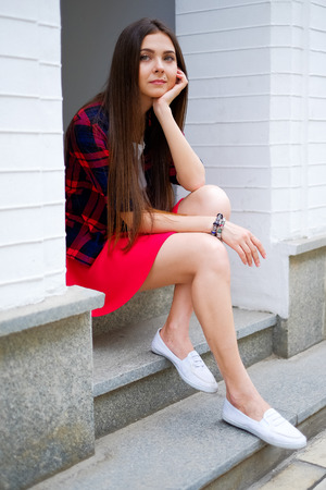 erotical: woman in skirt sitting on street. Beautiful long hair woman relax on street Stock Photo