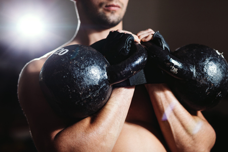 athlete with Kettlebells workout. handsome muscular man fitness workout in gym
