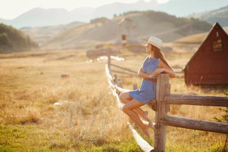 Sexy Frau posiert in Cowboy Hut auf Landschaft. reisende coutryside Berge und Wiese Hintergrund. Standard-Bild - 75987372