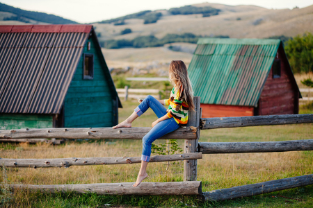 the enchantress: woman travel village alone. Authentic woman relax in countryside. Mountains and wooden house background.