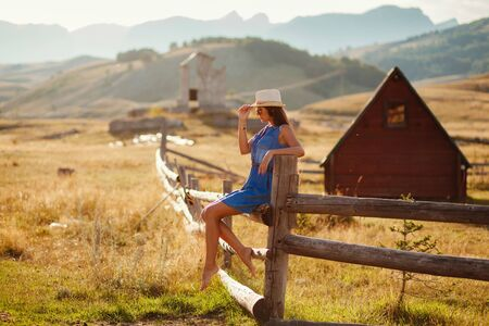 the enchantress: sexy woman travel countryside alone. Wooden houses and mountains background.