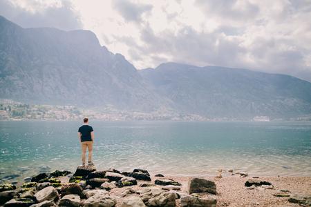 man travel rocky beach and mountains bay view. Kotor Bay, Montenegro Stock Photo