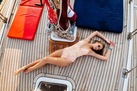 럭셔리 여자 바다에서 요트입니다. 수영복에 섹시 한 여자는 휴가에 요트 보트에 긴장.