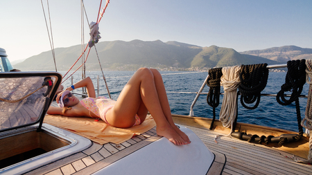 luxury woman relax on yacht boat. Sea waves and mountains background.