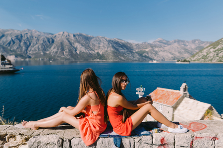 two girls relaxing on seashore with mountains view. Kotor Bay, Montenegro