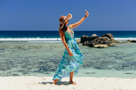 happy woman holding smartphone on beach in tropics. Female travel and use smartphone on beach of Seychelles.