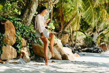 woman listen to music on beach and holding laptop. Summer vacation in Seychelles. Stock Photo