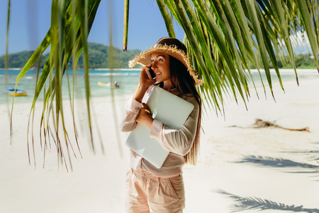 Woman talking on phone on beach in tropics. Working remotely while travelling. Summer vacation in Seychelles. Stock Photo
