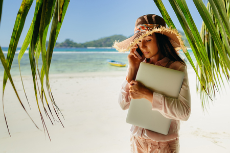 Woman talking on phone with laptop on beach. Working remotely while travelling. Summer vacation in Seychelles.