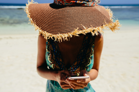 woman using smartphone on beach in tropics. Female travel and use smartphone on beach of Seychelles.