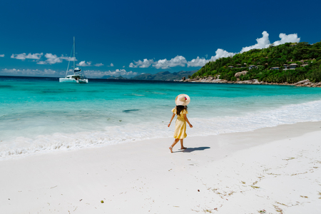 woman relax on tropical beach resort. Fashion sexy woman in summer dress and hat walking on beach of Seychelles.