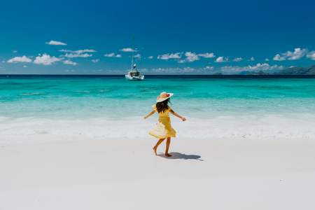 woman travel tropical beach resort with yacht view. Fashion sexy woman in sarong and hat walking on beach of Seychelles.