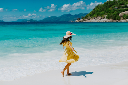 luxury woman travel tropical beach resort. Fashion sexy woman in sarong and hat walking on beach of Seychelles.