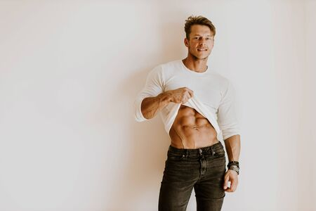 Brutal muscular man showing six pack abs muscles indoors. Brutal muscular man wearing white shirt showing abs muscles. Muscles and abs. Joyful male showing abs stomach at home wearing casual jeans Stock Photo