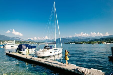 Beautiful woman walking on the pier near the yacht and boats with mountains view in Europe, Switzerland. Travelling in Europe. Sailing by yacht on vacations in Switzerland. Luxury lifestyle. Imagens