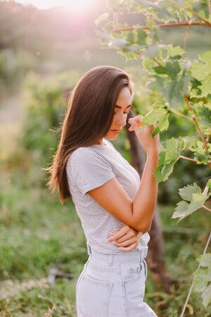 portrait of woman relaxing at countryside summer time. Caucasian long hair woman relax at countryside vineyard area at sunset. Italy