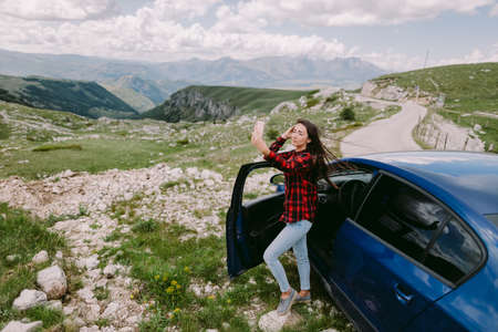 attractive woman travel by car and using smartphone in mountains