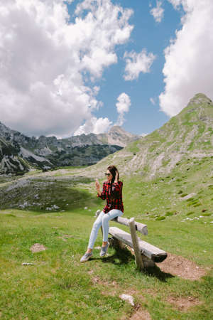 pretty woman traveller using smartphone in mountains