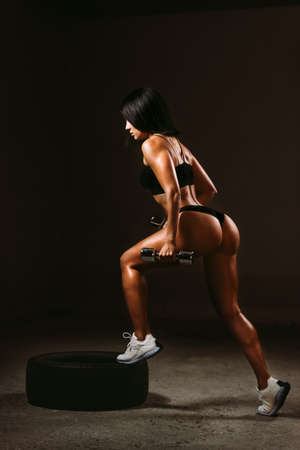 sexy fitness woman posing in underwear with dumbbells