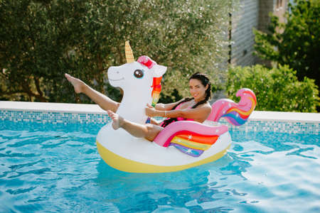 attractive woman relax in swimming pool on inflatable beach floaty toy unicorn in swimming pool