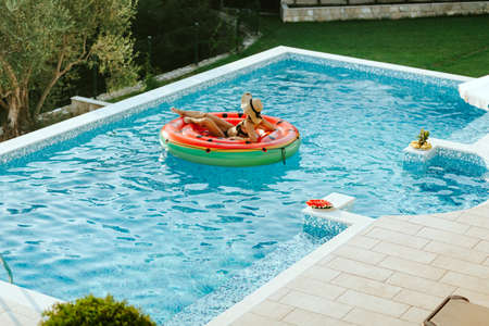 woman relax in swimming pool on inflatable pool toy Foto de archivo