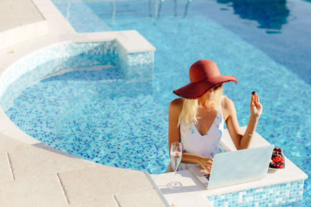 woman using laptop and work remotely near swimming pool