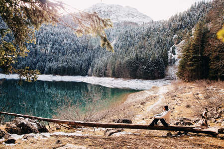 woman relax in winter forest with lake view and mountains in snow