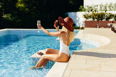 sexy woman relax in swimming pool and drinks champagne Stock Photo